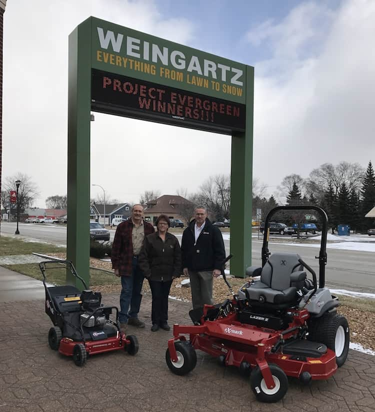 Joe and Barb Matney (left) of In Memory of Community Garden and the Warrendale Community Organization, and Dan Pagel of Exmark dealer Weingartz Utica, stand next to the mowers that will help maintain green spaces in the Detroit community.